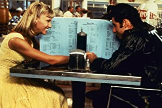 John Travolta and Olivia Newton-John in Grease seated in diner hiding behind menus 24x36 Poster