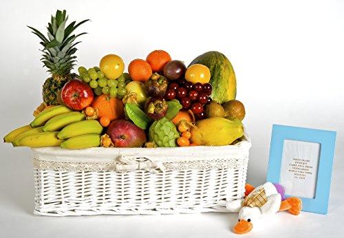 Cesta de frutas Bambino, con variedad mediterránea y tropical, sobre una cesta de estilo infantil y un marco de fotos de colores