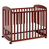 Product Image of the Davinci Alpha Mini Rocking Crib in Rich Cherry | Removable Wheels | Greenguard...