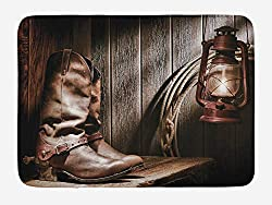 A decorative cowboy bath mat with lantern and cowboy boots