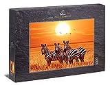 Ulmer Puzzleschmiede - Puzzle 'Bajo el sol de África': Puzzle de 1000 piezas - Un pequeño grupo de cebras bajo el sol en la sabana de África