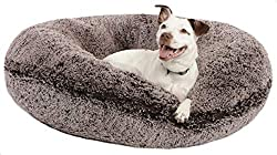 Small white dog laying on a brown plush donut bed.