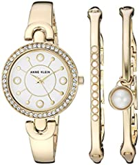 Bezel set with 48 clear Swarovski crystals; Mineral crystal lens; White glossy dial with gold-tone hands and faux pearl accented markers Gold-tone bangle with adjustable end links; Jewelry clasp and extender; Set includes two faux pearl accented bang...