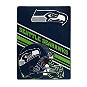 """Features a team helmet in the foreground and the team logo and name slanted in the background Soft and warm raschel fabric; oversized; decorative binding around all edges Measures 60""""W x 80""""L Machine wash cold separately using delicate cycle and mild..."""