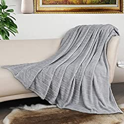 Light grey Bertte luxury fleece blanket covering a leather chair with wooden arms is included in this scopist holiday gift guide
