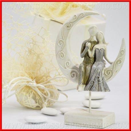 Figurine en résine colorée en forme de mariés stylisés, elle en robe argentée, lui bronze, qui se tiendra la main assis sur une demi-lune blanche décorée de lignes rondes (H 14 cm) – Bonbonnière de mariage, dragées (kit 12 pièces + boîte)