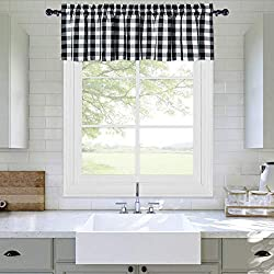 Farmhouse kitchen sink with black and white curtains over it.