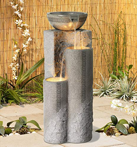 large pillar with bowl on top, water cascading from the bowl to a round pillar with opening below it and then water cascading from that pillar to another, shorter round pillar to the left.