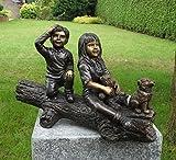 Bonita Figura de dos niños con su perro la en un árbol tronco...