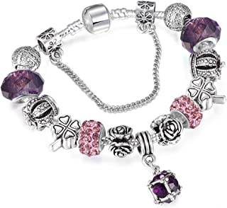 A 925 silver bracelet adorned with Pandora elements, beads, roses and a silver crown with a pendants shaped like a crystal...