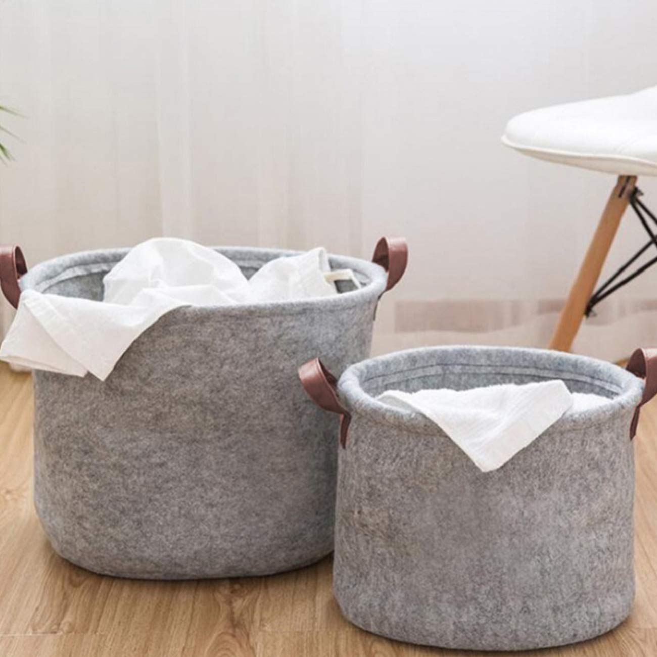 two felt storage baskets with handles and linens inside