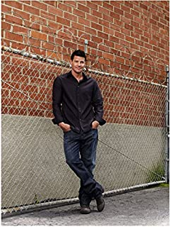 Bones (TV Series 2005 - ) 8 Inch x10 Inch Photo David Boreanaz Ankles Crossed Hands in Pockets Leaning Against Fence in Front of Brick Wall kn