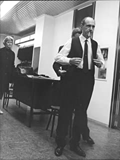 Vintage photo of Andreas G. Papandreou standing and a man readying him.