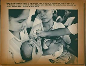 Vintage photo of Vaccination:a baby receive drops of vaccine.