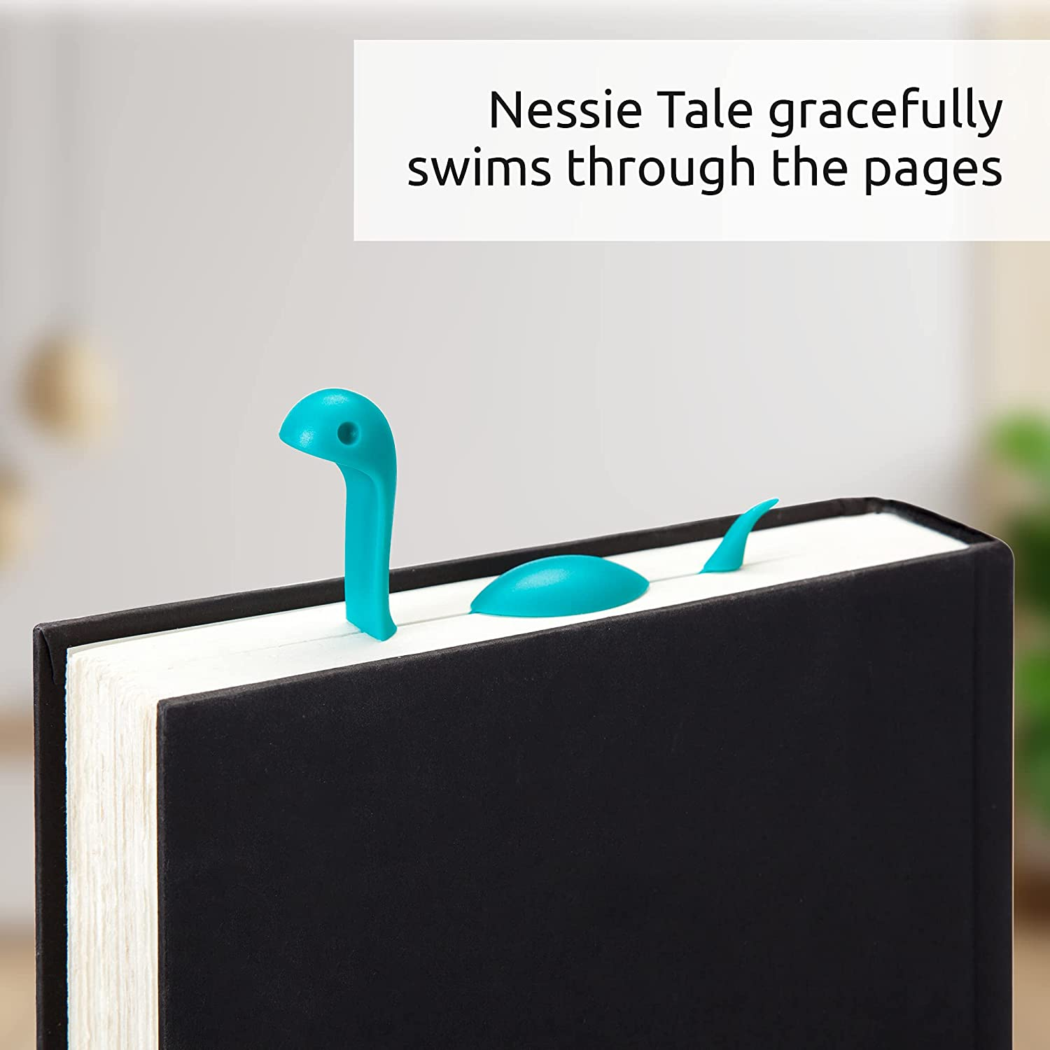 A closed book with a blue lochness monster bookmark peeking out at the top