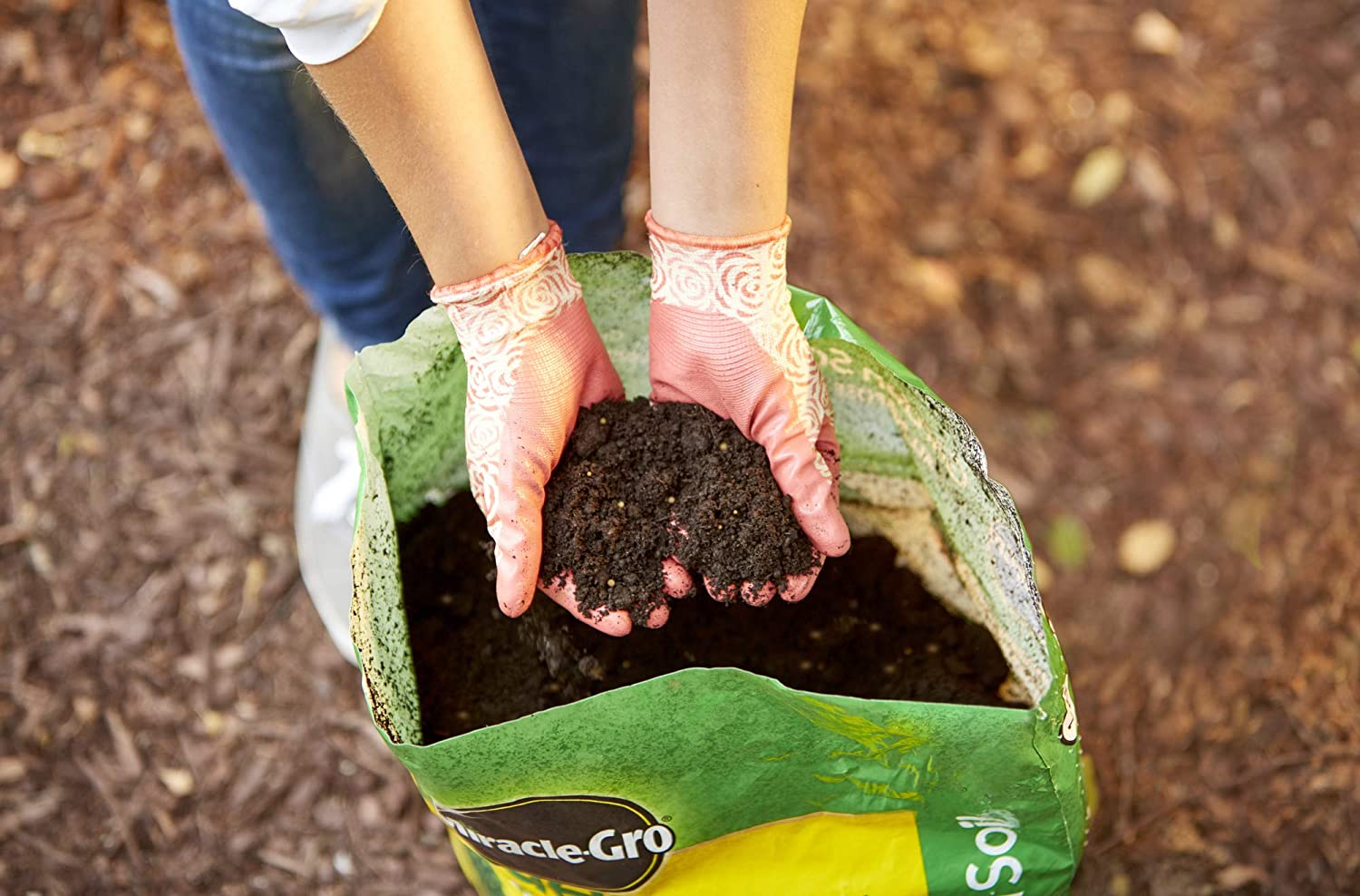 A woman showing the soil from the Miracle-Gro Potting Mix.