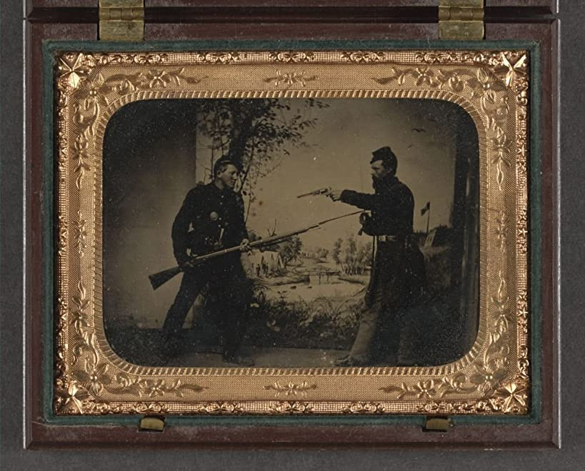 1861 Photo Two unidentified soldiers in Union uniforms posing with bayoneted Springfield Model 1861 rifled musket with attached bayonet, knife, and Colt Model 1851 Navy revolver in front of painted b