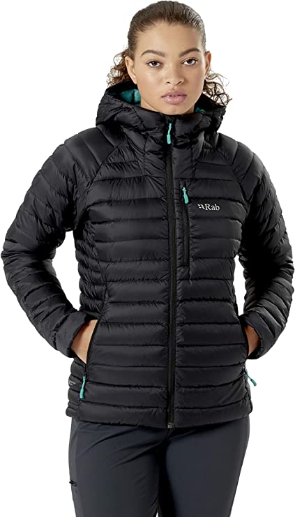 Image of a woman wearing a winter jacket in color black, with both hands inside the side pockets, looking at the camera.