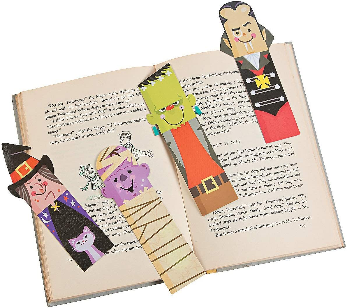 An open book with 4 laminated bookmarks on top. Each bookmark is a different Halloween figure: a witch, a mummy, frankenstein, and a vampire