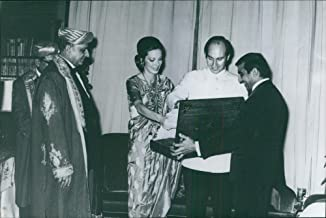 Vintage photo of Aga Khan IV with a woman looking at the suitcase and smiling.