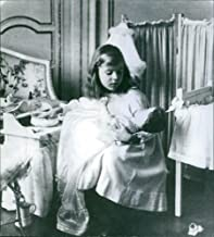 Vintage photo of A royal photo of Princess Ingrid of Sweden playing her doll in her room.