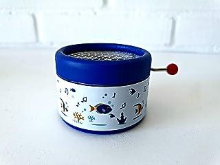 Caja de música azul decorada con dibujos de mar y la canción Hey Jude de los Beatles en una manivela manual