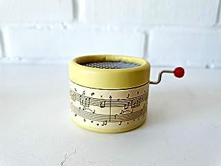 Caja de música amarilla decorada con escritura musical y la melodía Cumpleaños Feliz en manivela manual