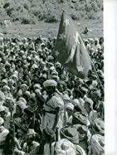 Vintage photo of Warriors of Mutawakkilite Kingdom of Yemen have gathered in a place during North Yemen Civil War in 1962, they hold rifle and listening something