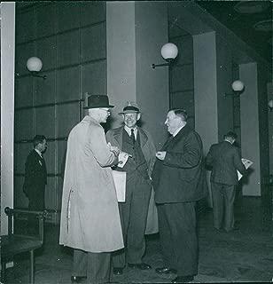 Vintage photo of Urho Kaleva Kekkonen communicating with other men standing beside him.