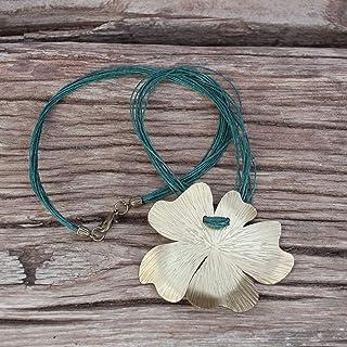 Collar flor color dorado, con textura y cordón de lino.