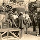 """Rob Wagner, back to camera, on the Paramount lot shooting """"Two Flaming Youths (1927) with assistant cameraman Al Williams, assistant director Otto Brower, and actors Jack Lundon and John Seresheff."""