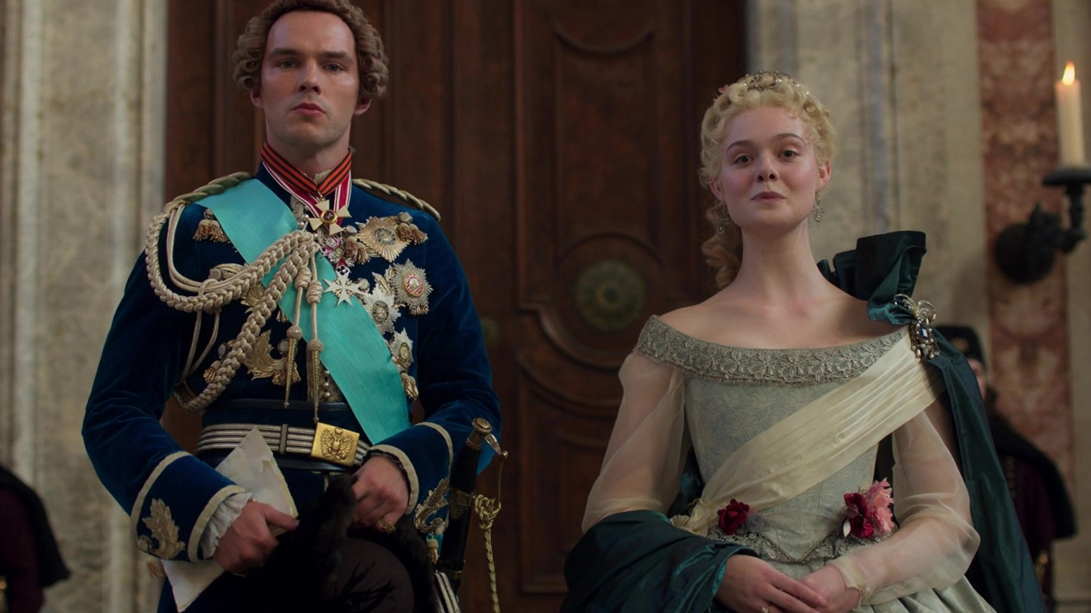 Nicholas Hoult and Elle Fanning in The Great (2020). Peter (left) and Catherine (right) and standing together in their royal attire, he in a navy velvet jacket adorned with gold medals and a blue sash, she in a more muted pale green dress with a cream sash and a forest green cloak over one shoulder. Both look into the camera, poised.