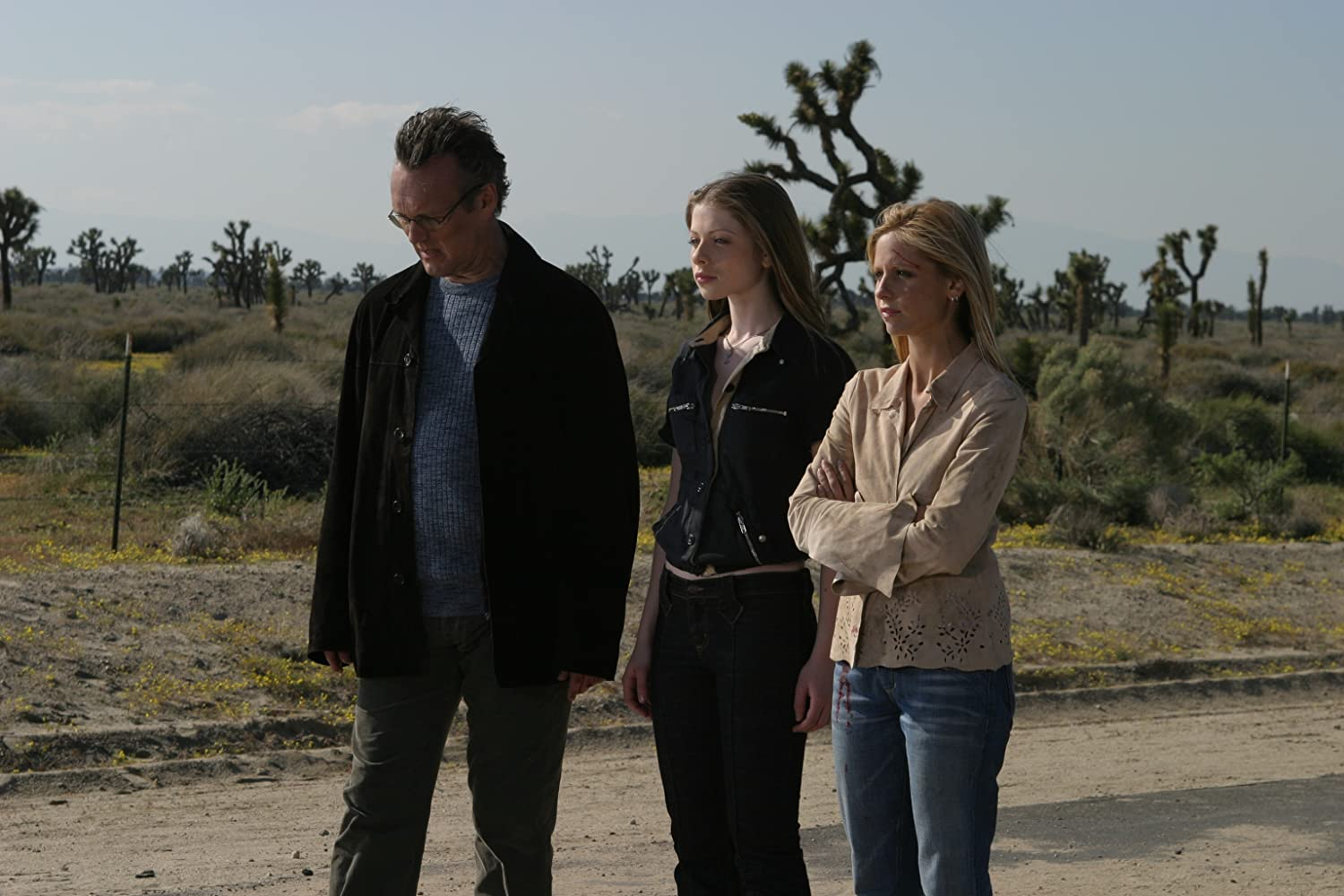 Sarah Michelle Gellar, Michelle Trachtenberg, and Anthony Head in Buffy the Vampire Slayer (1997). L-R Giles, Dawn, and Buffy stand on a dusty deserted highway, looking off to the left of the frame. They are all looking rather worse for wear – Buffy has a large red cut on her forehead and blood on her blue jeans, but she stands with her arms folded, resolute. Giles, the middle aged man with thinning grey hair and a black overcoat, looks down at the ground, meanwhile Dawn, a slim white girl with light brown hair, holds her head up high.