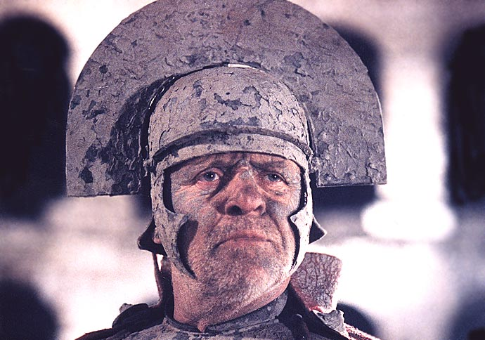 Anthony Hopkins as Titus Andronicus in Titus (1999). A close up of Titus' face, which is covered in a grey-coloured clay liquid which also stains his collar and war helmet. He is looking pensively into the distance, brows creased.