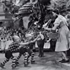 Judy Garland, Harry Earles, Jackie Gerlich, and Jerry Maren in The Wizard of Oz (1939)