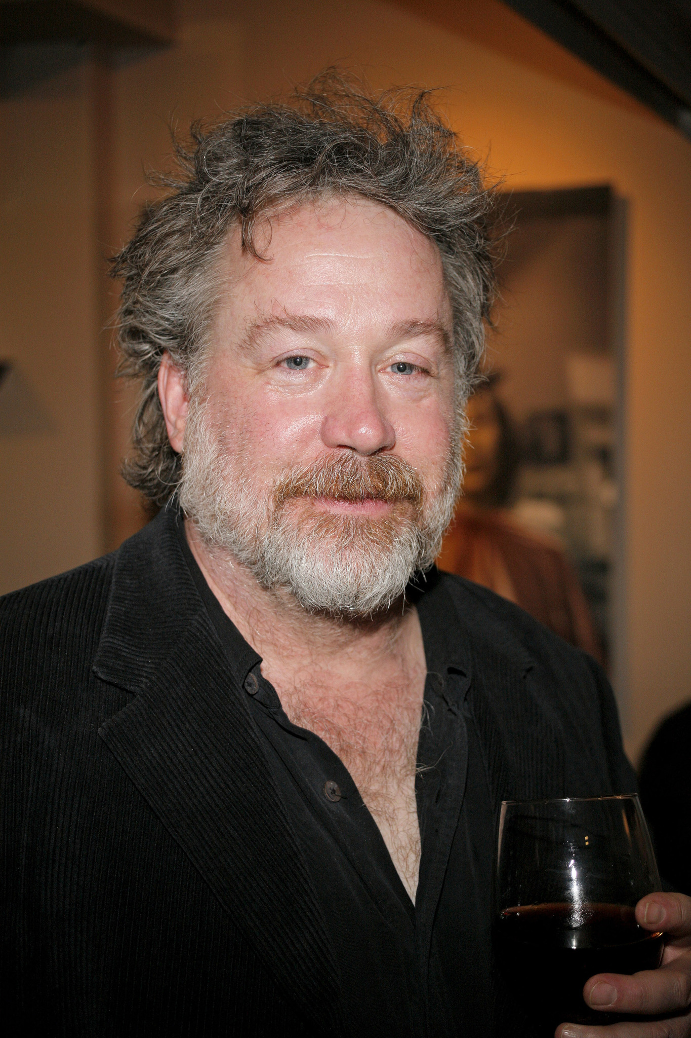 Tom Hulce is holding a wine glass in his hand