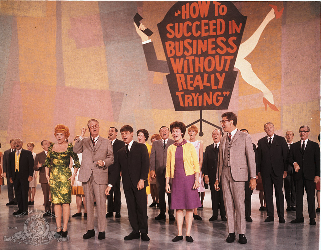 Maureen Arthur, Janice Carroll, Jeff DeBenning, Ruth Kobart, Michele Lee, Robert Morse, John Myhers, Kathryn Reynolds, Sammy Smith, Anthony 'Scooter' Teague, Rudy Vallee, and Carol Worthington in How to Succeed in Business Without Really Trying (1967)