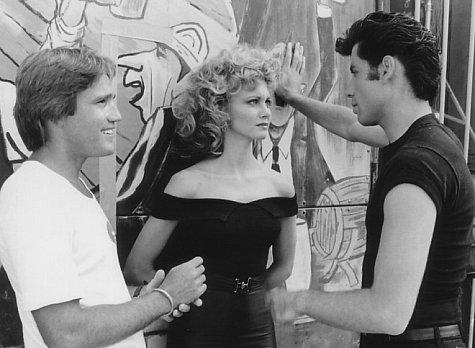 Director Randal Kleiser (left) with Olivia Newton-John (center) and John Travolta (right) on the graduation carnival set.