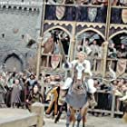 Amid the adrenaline-charged cries of spectators-including (from left to right, background) Kate (Laura Fraser), Chaucer (Paul Bettany) and Roland (Mark Addy), aspiring knight William (Heath Ledger, foreground) rides into fame