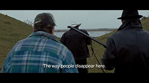 Robert Hansen is a cop in Copenhagen who makes a mistake, is remanded for therapy, then assigned to a small town in South Jutland, where cows and problems disappear into the mud. He quickly learns that the town bully, Jørgen, beats his wife, an outsider like Robert. He tries to get her to swear out a complaint against Jørgen; she flirts with Robert. When someone dies and Robert knows the prime suspect is innocent, he halts vigilante justice and things get complicated. He wants to protect himself and the daughter of Jørgen, and he wants to reconnect with his own daughter back home. Is rural justice his ticket back to Copenhagen? Is there any chance at happiness?