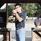 An expert marksman, Henri Miller practices at a shooting range while his son, Gary, watches.