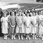 Respendent in their party dresses, Madeline (Hatty Jones, front row, far left) and her classmates attend Pepito's birthday party with the help of gift-toting Miss Clavel (Frances McDormand, far left).