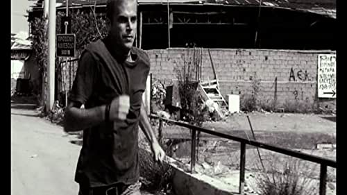 """Two teenage boys, a ticket inspector, a young couple, immigrants, children, all cornered at the end of a blind alley in the center of Athens. A black-and-white episodic film with standing-out aesthetics, spare, non-linear narration and tough language. Exclusion, violence, psychological cannibalism and consecutive power failures portray a society on the edge, """"forgotten in the dark"""" as noted by of the characters. As victims and villains switch roles, a mechanism stronger than their own volition is revealed: the meat grinder of bounced checks, empty bank accounts and bankrupt dreams that moves the action forward to the point of dead end.  The film speaks of the violence that surrounds us and the way in which we reproduce it. Essentially, the theme of the movie is the human body's conductivity of violence. It is an episodic film, composed of three different stories that intersect at several points. The first story is about a ticket inspector (Vangelis Mourikis), who is buried in debt and is looking for ways to get out of debt, but also to keep his family together. The second story is about a couple (Tasos Nousias - Kora Karvouni) that is one step away from breaking up. The third story is about two teenage boys (Omiros Poulakis - Promitheas Aliferopoulos), who wander around the city, carrying with them an old revolver (family heirloom). All three stories unfold within the time frame of a single day, during which the power is constantly down due to some strike. At the points when the three stories intersect, they also change direction. Victims become villains and vice-versa. Up until the final solution, where they all come face to face with the consequences of their actions."""