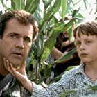 Morgan Hess (Rory Culkin, right) shows his father, Graham (Mel Gibson, left) what's going on.