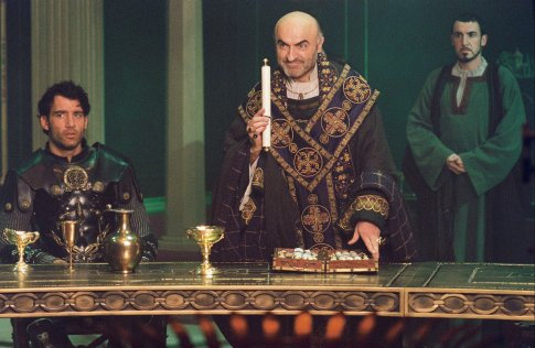 Arthur (Clive Owen, left) listens as Bishop Germanius (Ivano Marescotti, center) requests a final challenge of Arthur's Knights of the Round Table while Horton (Pat Kinevane, right) looks on.