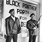 Founding members Bobby Seale (Courtney B. Vance) and Huey Newton (Marcus Chong) keep watch in front of Black Panther headquarters.