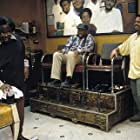 CEDRIC THE ENTERTAINER as Eddie, CARL WRIGHT as Checkers Fred, and ICE CUBE as Calvin hanging around the shop