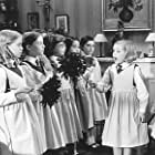 Madeline (Hatty Jones, second from right) and faithful helper Aggie (Clare Thomas, far right) instruct their schoolmates in the fine art of housecleaning.
