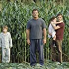 Graham Hess (Mel Gibson, center left), along with his son, Morgan (Rory Culkin, left), his daughter, Bo (Abigail Breslin, center right), and his brother, Merrill (Joaquin Phoenix, right), investigate the strange occurrence.