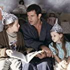 Graham (Mel Gibson, center) tries to calm his children, Morgan (Rory Culkin, left) and Bo (Abigail Breslin, right), who think that tin foil hats can stop aliens from reading their minds.